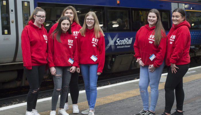 Group of young people stood by a train